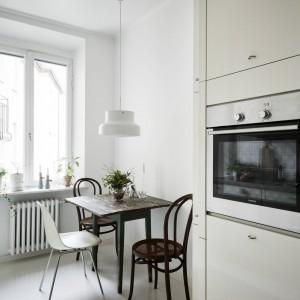 W rogu kuchni, ustawiono niewielki stół, przy którym posiłek mogą jednocześnie zjeść trzy osoby. Kącik jadalniany wprowadza do wnętrza element eklektyzmu. Stół i dwa ciemnobrązowe krzesła są utrzymane w klasycznej stylistyce, podczas, gdy trzecie białe krzesło nie tylko nawiązuje barwą do mebli kuchennych, ale także koresponduje mocniej z nowoczesnym stylem. Fot. Stadshem.