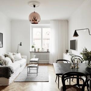Monochromatyczność salonu urozmaica drewniana podłoga i wyeksponowana na tle białego sufitu lampa w metalowym kloszu w miedzianym odcieniu. W rogu pomieszczenia ustawiono składany stół, które w razie potrzeby można złożyć i uzyskać więcej miejsca. Przytulnym akcentem jest kanapa, udekorowana stosem poduszek. Fot. Stadshem.