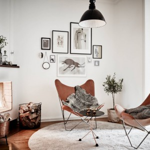 W otoczeniu kominka ustawiono dwa wygodne fotele i ułożono przytylny dywan. Domownicy mogą usiąść i zrelaksować się przy ciepłych płomieniach. Fot. Stadshem.