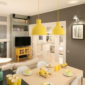 W obrębie jednej przestrzeni udało się urządzić aneks kuchenny, jadalnię i salon. Wnętrze utrzymano w stonowanych barwach z jednym mocnym, czarnym akcentem. Aranżację ożywiają żółte lampy nad stołem. Projekt: Lucyna Kołodziejska. Fot. Bartosz Jarosz.