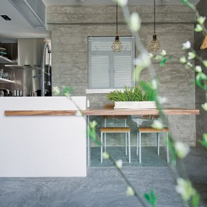 Biała wyspa kuchenna pięknie komponuje się z połączonym z nią drewnianym blatem i dopasowanymi do niego krzesłami. Na niewielkiej przestrzeni połączono funkcję powierzchni zmywania i jadalni. Projekt: Millimeter Interior Design. Fot. Millimeter Interior Design.