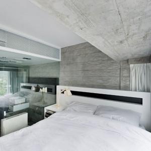 Sypialnia zachwyca światłem, jasnymi kolorami i nowoczesnymi formami. W obrębie pomieszczenia, w narożnym kubiku, zlokalizowano łazienkę, odgrodzoną od pokoju sypialnego szklanymi, przezroczystymi ściankami. Projekt: Millimeter Interior Design. Fot. Millimeter Interior Design.