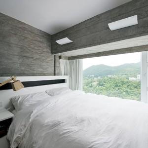 Z sypialni roztacza się piękny widok na okolicę. Panoramiczne okno, przy którym zlokalizowano łóżko oprócz pięknych widoków, zapewnia bogaty dostęp światła. Projekt: Millimeter Interior Design. Fot. Millimeter Interior Design.
