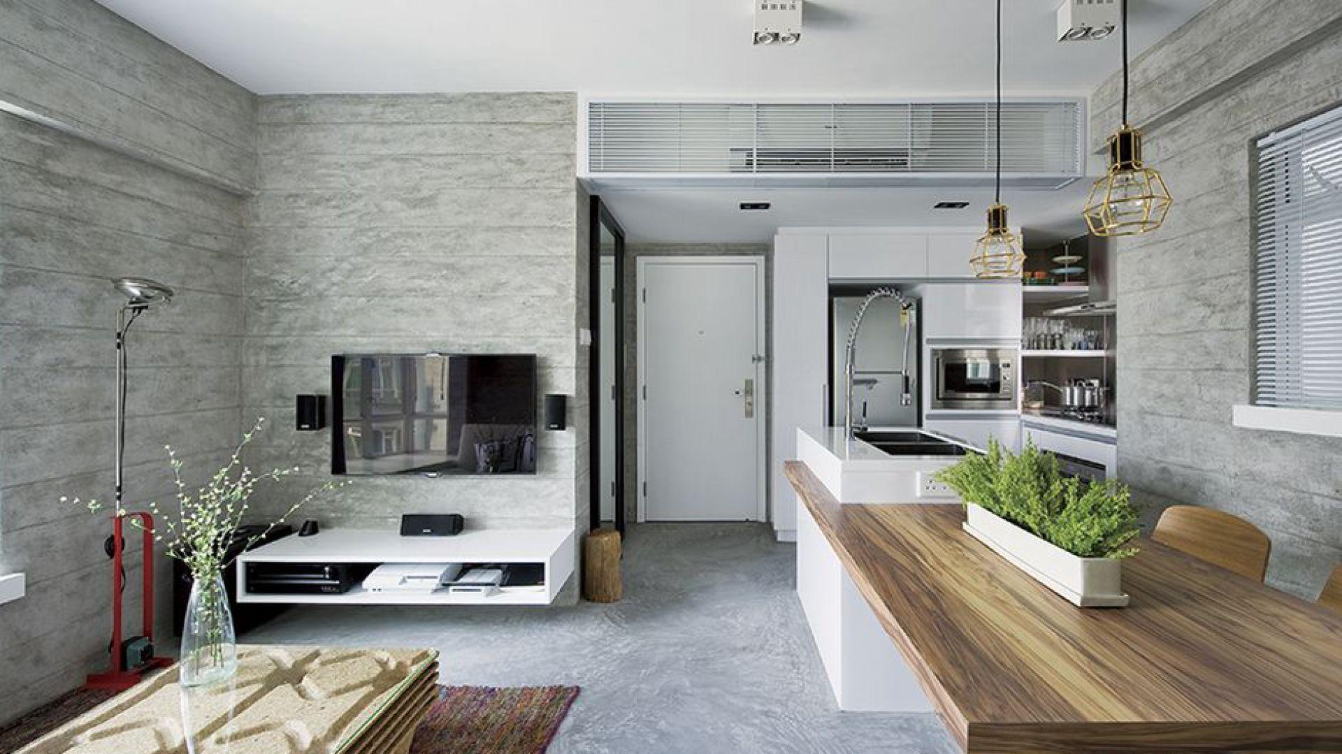 Szafka RTV w salonie dopasowana została stylistycznie i kolorystycznie do białej zabudowy i wyspy w kuchni. Ciekawy efekt do wnętrza wprowadza stolik kawowy, którego blat stanowi tafla szkła, a korpus wykonano z wielowarstwowego betonu. Projekt: Millimeter Interior Design. Fot. Millimeter Interior Design.