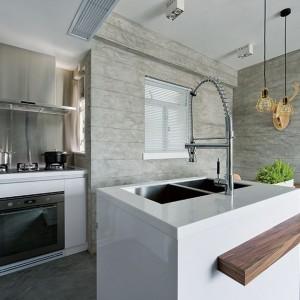 Piekarnik z płytą kuchenną i okapem wpasowano w niewielką wnękę w kuchni. Po jej lewej stronie poprowadzono wysoką zabudowę. W rogu zaplanowano praktyczne półki. Ściana nad płytą kuchenną pokryta została panelem stalowym. Projekt: Millimeter Interior Design. Fot. Millimeter Interior Design.