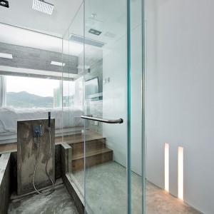 Piękna, nowoczesna łazienka została wykończona w szkle i betonie. Jej ściany stanowią wielkoformatowe przeszklenia, a strefę kąpielową, w której zmieszczono prysznic i wannę, surowy beton. Projekt: Millimeter Interior Design. Fot. Millimeter Interior Design.