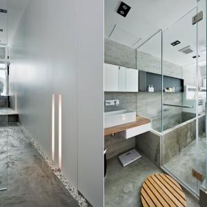 Do sypialni i łazienki prowadzi przedpokój, którego podłogę wyłożono ozdobnymi, białymi kamieniami i pokrywającą je częściowo, jednolitą warstwą betonu. Projekt: Millimeter Interior Design. Fot. Millimeter Interior Design.