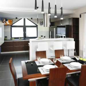Nowoczesne, czarno-białe oświetlenie efektownie kontrastuje z ciepłym kolorem stołu i krzeseł. Projekt: Marta Kilan. Fot. Bartosz Jarosz.