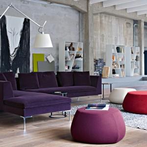 Wygodna sofa z kolekcji Charles włoskiej marki B&B Italia na smukłych, stalowych nóżkach. Towarzystwa dotrzymują jej owalne pufy. Fot. B&B Italia.