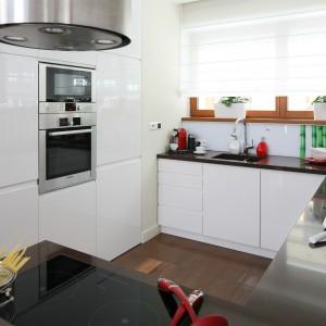 Białe meble kuchenne i czerwone dodatki dekoracyjne komponują się z białymi meblami wypoczynkowymi oraz zasłonami w salonie. Projekt: Katarzyba Mikulska-Sękalska. Fot. Bartosz Jarosz.