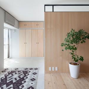 Wysokie szafki, zlokalizowane w sąsiedztwie sypialni oferują sporą powierzchnię do przechowywania. Wykonane z drewna w tym samym kolorze co podłogi i element działowy, harmonijnie wpasowały się we wnętrze. Wbudowane w ścianę, są jedynie dyskretnie zaakcentowane. Projekt: Chikara Ohno/Sinato. Fot. Toshiyuki Yano.