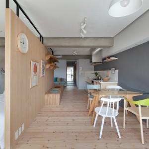 Na drewnianej zabudowie, pełniącej rolę ścianki działowej możemy powiesić ubrania czy dekoracje. Multifunkcyjny mebel jest niezaprzeczalnym punktem centralnym mieszkania. Projekt: Chikara Ohno/Sinato. Fot. Toshiyuki Yano.