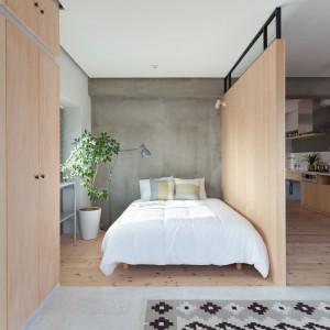 Sypialnię tworzy podwójne łóżko, ustawione w przestrzeni wyznaczonej przez drewnianą podłogę i ściankę działową. Z dominującym w kąciku drewnem kontrastuje elegancko surowa betonowa ściana. Projekt: Chikara Ohno/Sinato. Fot. Toshiyuki Yano.