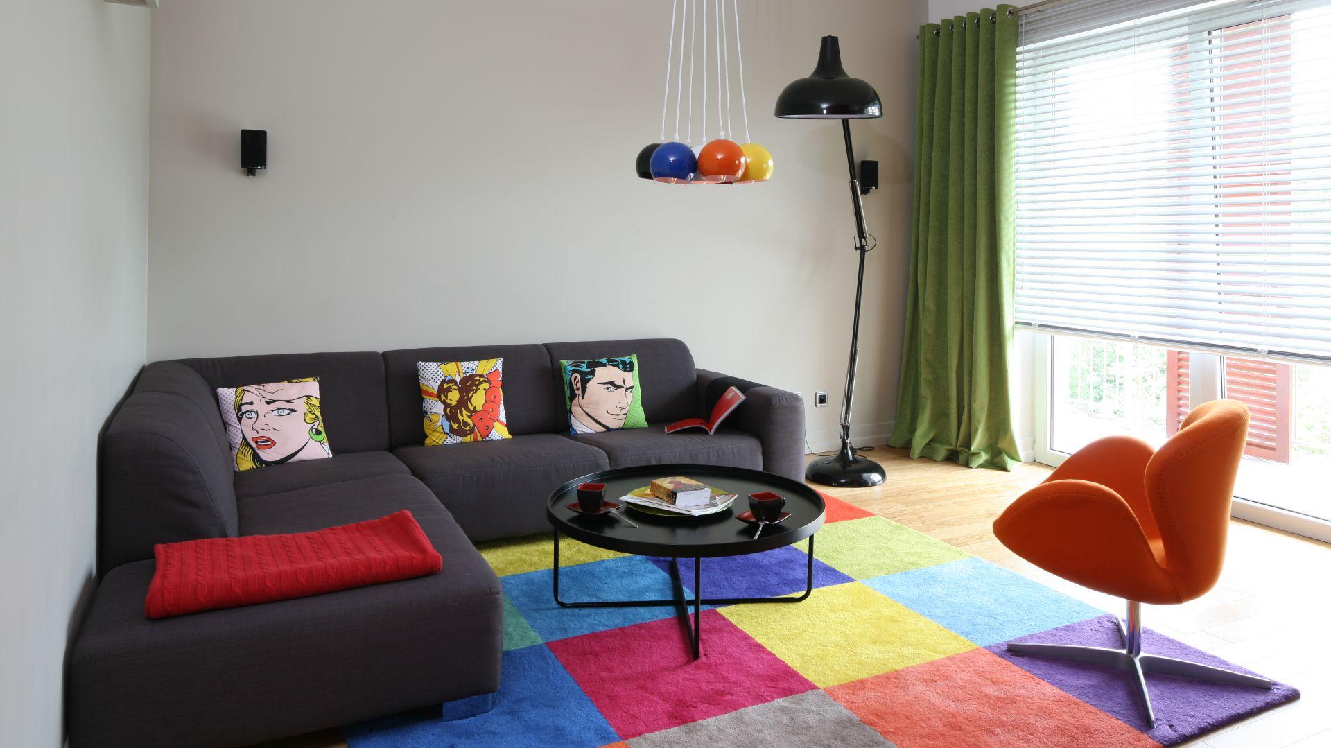 Pomarańczowy fotel przypominający kształtem rozkwitający kwiat koresponduje kolorystycznie z dywanem oraz lampą sufitową. Projekt: Dorota Szafrańska. Fot. Bartosz Jarosz.