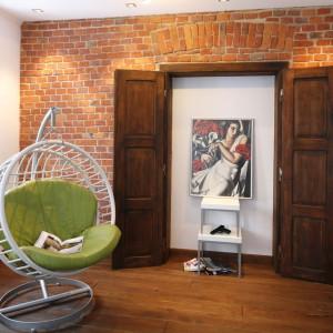 Zawieszony na stelażu bujany fotel z okrągłym siedziskiem ustawiono w rogu salonu. Można w spokoju, troszkę na uboczu, poczytać książkę jak również widać z niego obraz wyświetlany w telewizorze. Projekt: Konrad Grodzińki. Fot. Bartosz Jarosz.
