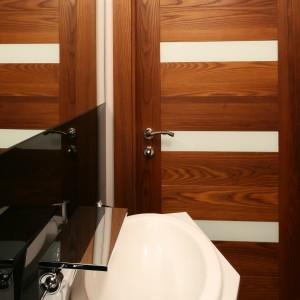 Ciepłe drewno, dodające surowemu wnętrzu przytulności, wręcz znakomicie pasuje do zimnych, ale wyjątkowo eleganckich, czarnych płytek na ścianie. Całość dopełnia biała ceramika. Projekt: Chantal Springer. Fot. Bartosz Jarosz.