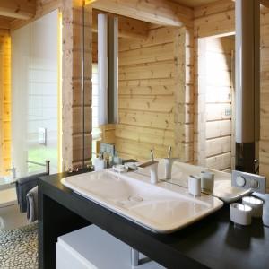 Cały dom zbudowany jest z bali, stąd obecność surowego drewna także na ścianach i suficie łazienki. Projekt: Tomasz Motylewski, Marek Bernatowicz. Fot. Bartosz Jarosz.