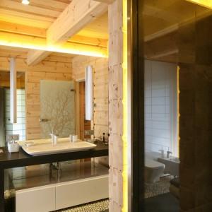 Dominującym elementem w tej łazience jest drewno, które nadaje charakter i styl całej aranżacji. Perfekcyjnie zestawiono je z nowoczesnym wyposażeniem oraz czarną płytą bazaltową w postaci blatu umywalkowego. Projekt: Tomasz Motylewski, Marek Bernatowicz. Fot. Bartosz Jarosz.