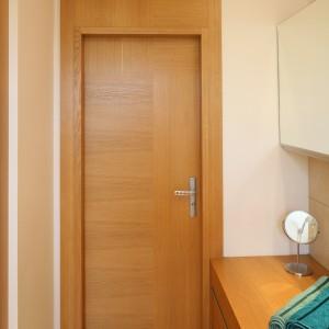 Także drzwi i ich obudowa zostały wykonane z drewna o ciepłym wybarwieniu. Projekt: Marcin Lewandowicz. Fot. Bartosz Jarosz.