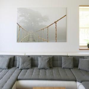 Mariaż bieli  oraz dekoru odwzorowującego rysunek drewna stanowi podstawę aranżacji całego domu, jednak w każdym pomieszczeniu materiały wykończeniowe zastosowano w różnych proporcjach. W salonie dominują ciepłe, drewnopodobne okładziny ścian, podłogi oraz wykończenia mebli. Biel ustępuje miejsca szarości, która wygodnie rozsiadła się na kanapach. Projekt: Małgorzata Błaszczak. Fot. Bartosz Jarosz.