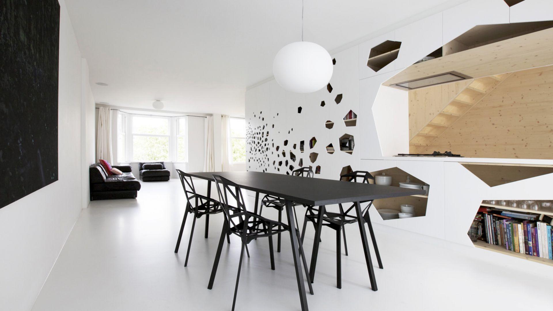 Efektowne białe panele, pokrywające zabudowę kuchenną, pełnią rolę oryginalnego elementu dzielącego umownie przestrzeń. Designerskie krzesła projektu Magis Constantin Grcic komponują się stylistycznie z otworami w panelach. Projekt: i29 interior architects. Fot. i29 interior architects.