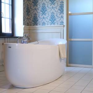 Jak w tradycyjnej angielskiej łazience ściany zostały pokryte piękną tapetą z charakterystycznym, kwiatowym dekorem, zaś w dolnej części – zabudowane wykonanymi przez stolarza, drewnianymi lamperiami. Projekt: Maciej Bołtruczyk. Fot. Monika Filipiuk-Obałek.