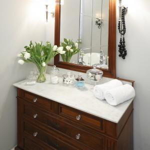Ważnym elementem wnętrza jest także drewniana komoda zakupiona w komplecie z lustrem. Zwieńczona marmurowym blatem pełni rolę toaletki. Projekt: Iwona Kurkowska. Fot. Bartosz Jarosz.