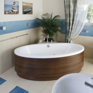 Salon kąpielowy dekorują ozdoby ścienne z morskimi motywami, a główny element aranżacji stanowi owalna wanna wolno stojąca w fornirowanej obudowie. Projekt: Marta Kruk. Fot. Bartosz Jarosz.