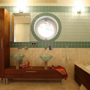 Niezwykłą dekoracją łazienki dla młodzieży jest okrągłe okno, które - niczym okrętowy bulaj - przywołuje opowieści o dalekich wyprawach. Morski odcień płytek otaczających okno, powtarza się także na szklanych umywalkach. Projekt: Mariola Świgulska, Radosław Świgulski. Fot. Marcin Onufryjuk.