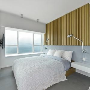 W sypialni wzrok przyciąga duże, podwójne łóżko, tekstylny zagłówek oraz efektowny panel na ścianie za łóżkiem. Funkcję nocnych szafek pełnią estetyczne, kubistyczne półki. Całość wnętrza utrzymano w bieli, ocieplonej brązowymi akcentami. Projekt: Millimeter Interior Design. Fot. Millimeter Interior Design.