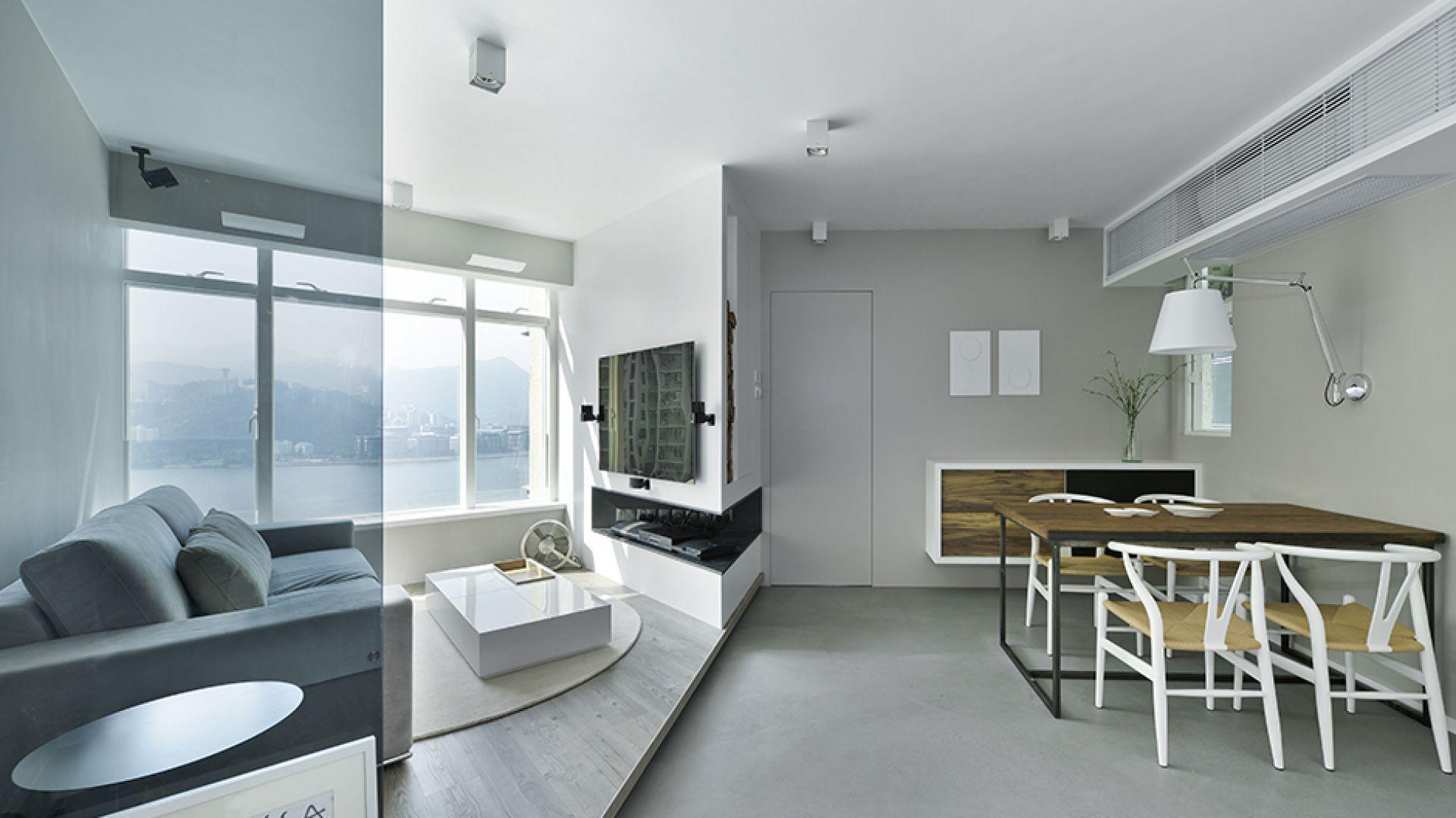 Salon i jadalnia zostały zlokalizowane w obrębie jednego pomieszczenia. Przestrzeń wypoczynkową wyznacza podniesiona podłoga oraz lekkie przeszklenie. Projekt: Millimeter Interior Design. Fot. Millimeter Interior Design.