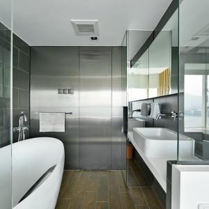 Jedną ze ścian w łazience w całości pokryto metalowymi panelami. Oprócz zyskanego futurystycznego klimatu, osiągnięto również efekt powiększonego optycznie wnętrza - dzięki połyskującej powierzchni ściany. Łazienkę wizualnie powiększa również lustro nad umywalką. Projekt: Millimeter Interior Design. Fot. Millimeter Interior Design.