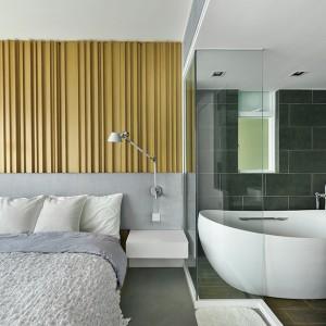 Otwarta na sypialnię łazienka ma charakter eleganckiego salonu kąpielowego z wolnostojącą wanną. Projekt: Millimeter Interior Design. Fot. Millimeter Interior Design.