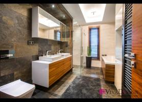 Zdjęcie łazienki z płytkami imitującymi drewno.
