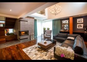 Zdjęcie salonu z widokiem na kominek obłożony betonem architektonicznym, dużą sofę oraz antresolę.
