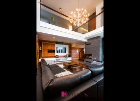 Zdjęcie salonu z widokiem na kominek obłożony betonem architektonicznym, dużą sofę, antresolę oraz ścianę telewizyjną.