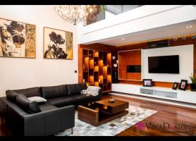 Zdjęcie salonu z widokiem na dużą sofę, antresolę oraz ścianę telewizyjną.