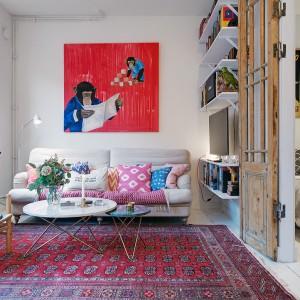 W salonie panuje radosny, optymistyczny klimat. Kolorowe, wzorzyste tekstylia oraz zabawny obraz z szympansami na czerwonym tle, nadają pomieszczeniu wyjątkowy charakter. Fot. Alvhem Makleri & Interior / Fredrik J Karlsson, SE360.