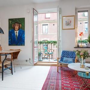 Symboliczną granicę pomiędzy salonem a jadalnią wyznaczają drzwi balkonowe. Fotel z drewnianymi poręczami nogami koresponduje ze stołem i krzesłami w jadalni. Fot. Alvhem Makleri & Interior / Fredrik J Karlsson, SE360.