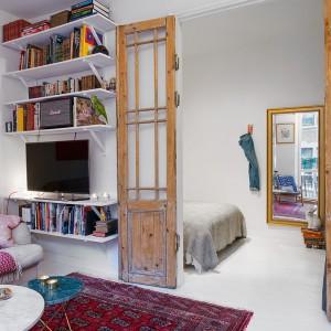 Z salonu do sypialni prowadzą podwójne, drewniane drzwi. Surowe drewno i przeszklenia ze szprosami czynią z nich oryginalny element dekoracyjny wnętrza. Na niewielkiej ściance zlokalizowano kącik telewizyjny i biblioteczkę. Fot. Alvhem Makleri & Interior / Fredrik J Karlsson, SE360.