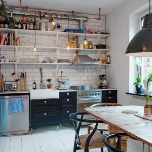 Funkcję kuchni pełni niewielki aneks kuchenny. W jego obrębie zmieszczono piekarnik z płytą kuchenną, zlewozmywak, blat kuchenny, a nawet zmywarkę! Podręczne sprzęty kuchenne i przyprawy można postawić na praktycznych półkach, pokrywających całą ścianę nad powierzchnią roboczą. Fot. Alvhem Makleri & Interior / Fredrik J Karlsson, SE360.