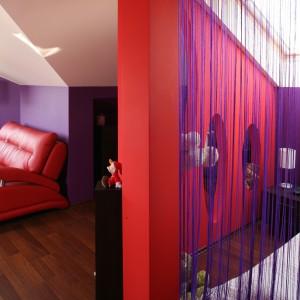 Niewielką sypialnię ukryto za dekoracyjną kotarą, wykonaną z firanki typu spagetti. Fot. Bartosz Jarosz.