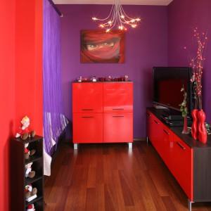 Przy strefie sypialnej ustawiono nowoczesną komodę i szafkę RTV w czerwonym kolorze. Fot. Bartosz Jarosz.