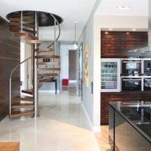 Kuchnia jest świetnie skomunikowana z całym domem - to tutaj krzyżują się trasy komunikacyjne. Zaledwie kilka kroków od wyspy kuchennej znajduje się korytarz z prowadzącymi na piętro schodami. Projekt: Katarzyna Koszałka. Fot. Bartosz Jarosz.