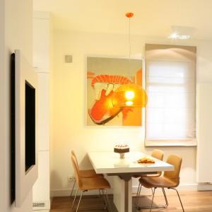 Lampa w pomarańczowym kolorze, zawieszona nad stołem jadalnianym, podkreśla apetyczny charakter tej strefy. Fot. Bartosz Jarosz.