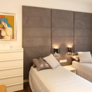 Sypialnia z dekoracyjnym, szarym zagłówkiem, którym wykończono ścianę za łóżkiem na całej długości. Projekt: Małgorzata Galewska. Fot. Bartosz Jarosz.