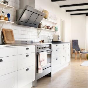Urokliwy i praktyczny aneks kuchenny. Lekko frezowane fronty białych mebli zdobią efektowne, kontrastujące z bielą uchwyty. Nad blatem kuchennym praktyczne półki na niezbędne przybory kuchenne. Fot. Ballingslov.