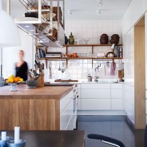 Funkcjonalna kuchnia, w której bardzo poważnie potraktowano aspekt funkcjonalności mebli kuchennych. Nad wyspą i aneksem zlokalizowano praktyczne półki - tak aby wszystko co niezbędne zawsze było pod ręką. Wygodę i funkcjonalność utrzymano w bieli i ocieplającym ją drewnie. Fot. Ballingslov.