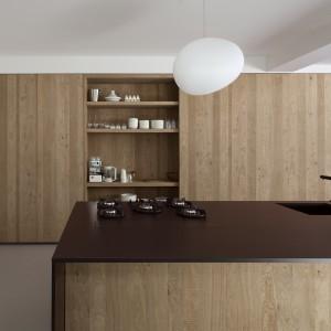 Mieszkanie urządzono w minimalistycznej, oszczędnej stylistyce. W kuchni - zamiast mnogości półek i szafek, postawiono na jednorodną wysoką, drewnianą zabudowę. Projekt: i29 interior architects. Fot. Ewout Huibers.