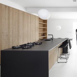 Ścianę w kuchni pokrywa zabudowa robiona na zamówienie, wykonana z dębowego, surowego drewna. Drewniane powierzchnie efektownie kontrastują z czarną wyspą kuchenną. Na gładkim blacie zlokalizowana nowoczesną płytę kuchenną oraz podblatowy zlewozmywak. Projekt: i29 interior architects. Fot. Ewout Huibers.
